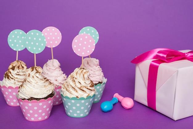 Grupo de cupcakes ao lado do presente