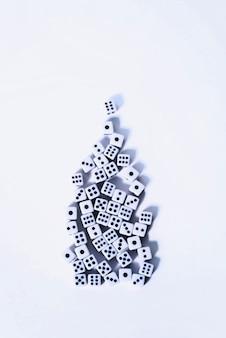 Grupo de dadinhos brancos empilhados sobre um fundo branco na forma de uma árvore de natal.
