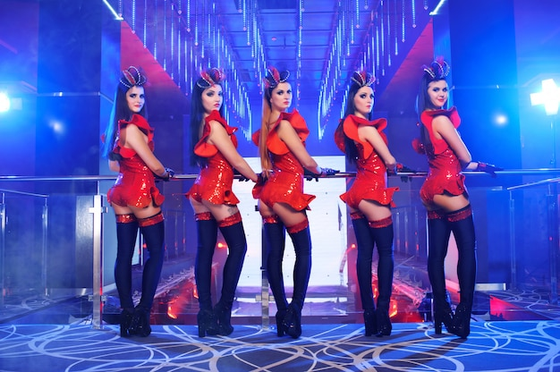 Grupo de dançarinas sexy no desempenho de roupas correspondentes vermelho