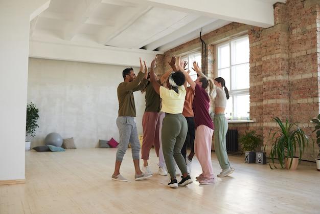 Grupo de dançarinos dando high five durante o treinamento no estúdio de dança