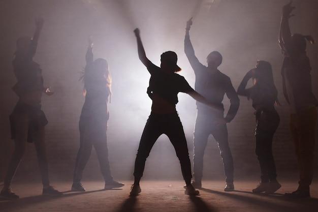 Grupo de dançarinos de rua realizando movimentos diferentes na rua escura.
