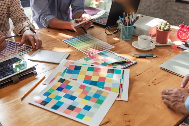 Grupo de designers asiáticos de brainstorming trabalhando em conjunto com colegas e amostras de cores