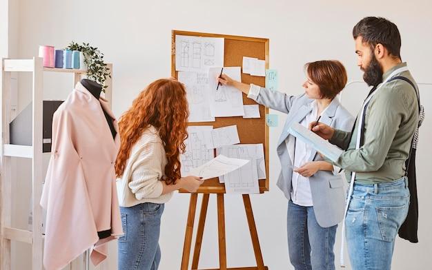Grupo de designers de moda apresentando ideias para linha de roupas