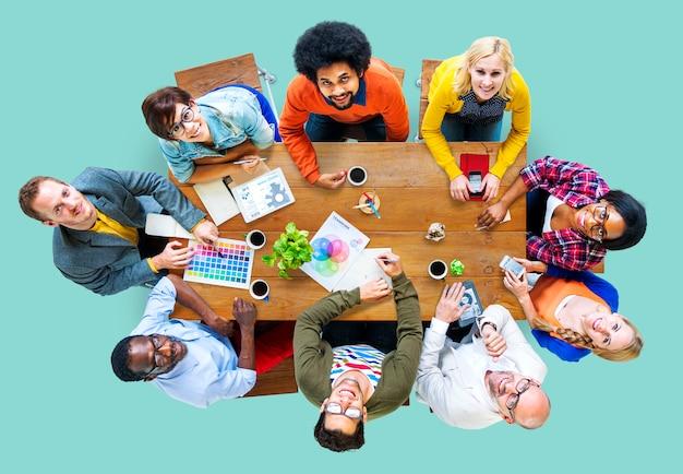 Grupo de designers diversos, tendo um conceito de reunião