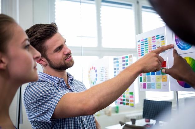 Grupo de designers gráficos que interagem sobre a carta de cor