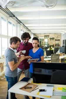 Grupo de designers gráficos que usa a tabuleta digital ao mesmo tempo tomando café