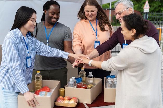 Grupo de diferentes pessoas oferecendo-se como voluntário em um banco de alimentos para pessoas pobres
