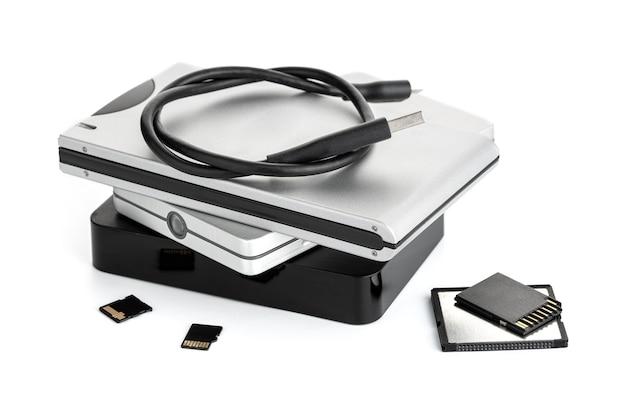 Grupo de discos rígidos externos e cartões de memória isolados na superfície branca. conceito de armazenamento de dados
