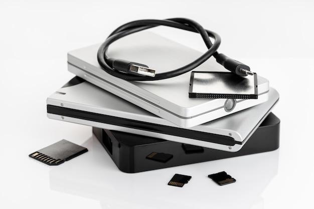 Grupo de discos rígidos externos e cartões de memória na mesa branca. conceito de armazenamento de dados