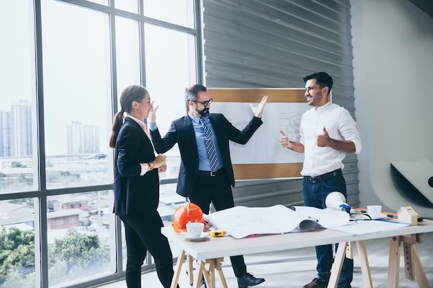 Grupo de discussão do engenheiro no escritório do canteiro de obras