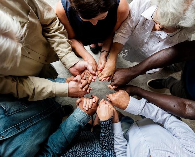 Grupo de diversas mãos abraçados