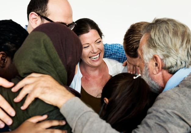 Grupo de diversas pessoas abraçadas a outras