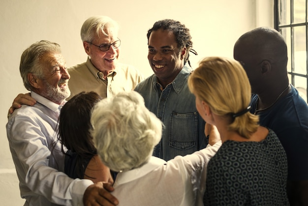 Grupo de diversas pessoas, apoiando-se mutuamente
