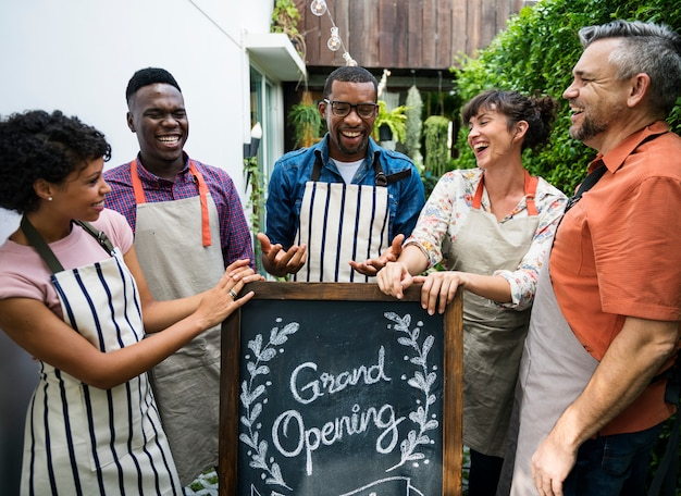 Grupo de diversas pessoas com placa de inauguração da loja