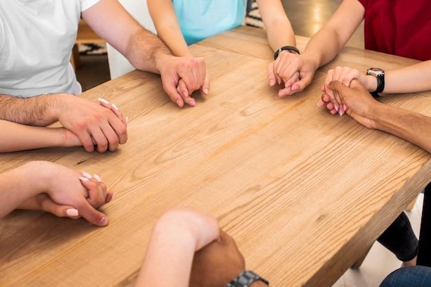Grupo de diversas pessoas de mãos dadas na mesa de madeira