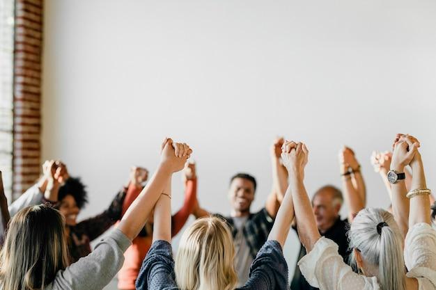 Grupo de diversas pessoas de mãos erguidas no ar