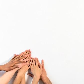 Grupo de diversas pessoas empilhando as mãos contra o pano de fundo branco