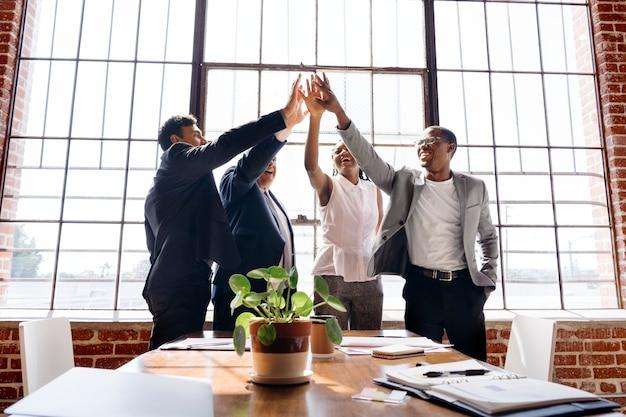 Grupo de diversas pessoas empilhando as mãos no meio