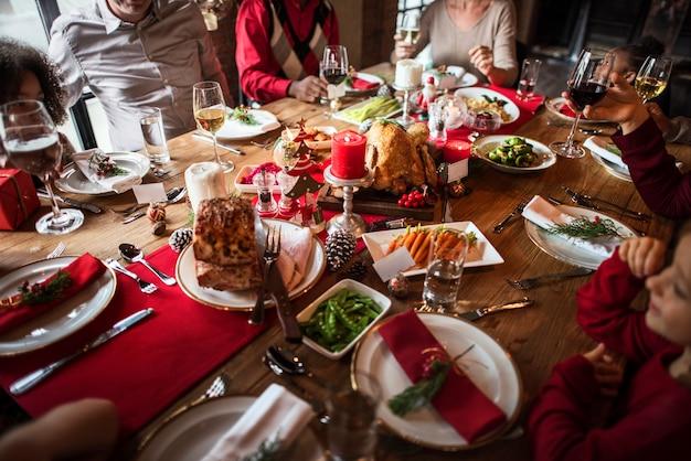 Grupo de diversas pessoas estão comemorando o feriado de natal