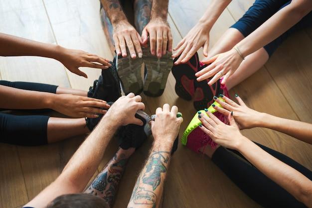 Grupo de diversas pessoas estão se juntando a uma aula de ioga