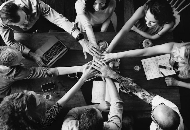 Grupo de diversas pessoas juntando as mãos em equipe