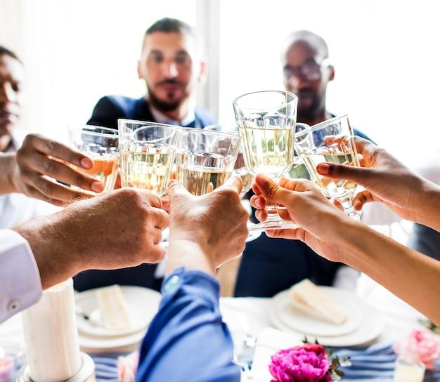 Grupo de diversas pessoas tilintando de copos de vinho juntos