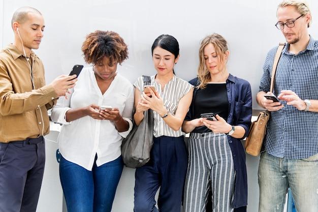Grupo de diversas pessoas usando smartphones