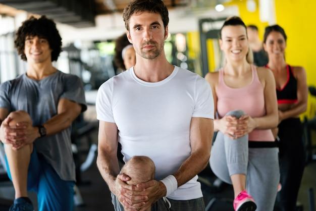 Grupo de diversidade de pessoas treinando em uma academia. treinador e pessoas em boa forma física se exercitando em uma aula de ginástica