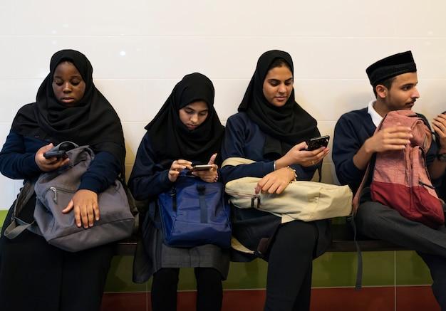 Grupo de diversos alunos usando telefones celulares