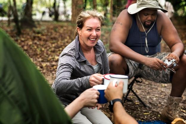 Grupo de diversos amigos, acampar na floresta