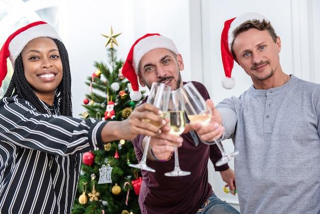 Grupo de diversos amigos comemorando o natal em casa, fazendo um brinde