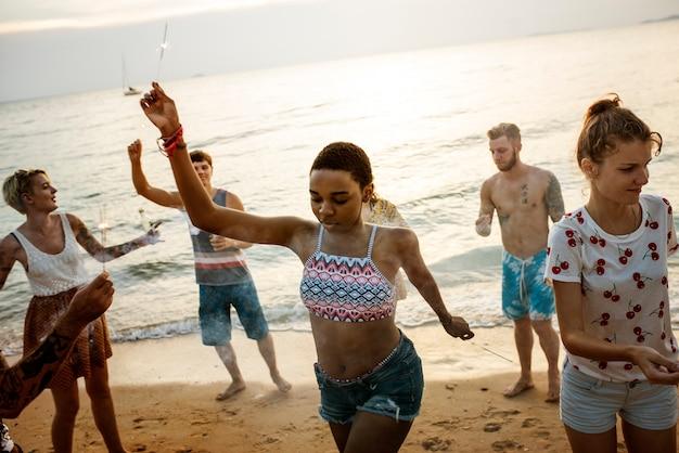 Grupo de diversos amigos desfrutando de estrelinhas na praia juntos