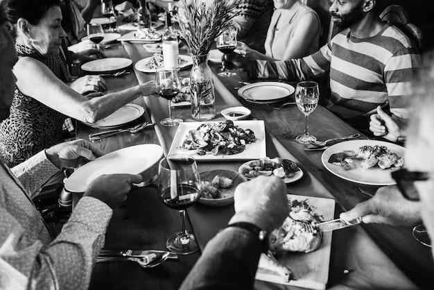 Grupo de diversos amigos, jantando juntos