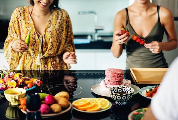 Grupo de diversos amigos preparando churrasco na cozinha juntos