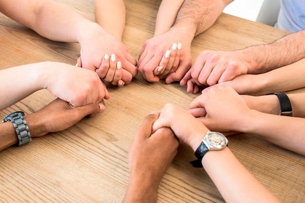 Grupo de diversos amigos, segurando suas mãos juntas sobre a mesa de madeira
