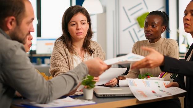 Grupo de diversos empresários reunidos para debater ideias sobre o novo projeto de finanças de papelada, colegas trabalhando juntos planejando o trabalho em equipe de estratégia de sucesso, sentado na mesa em um escritório moderno.