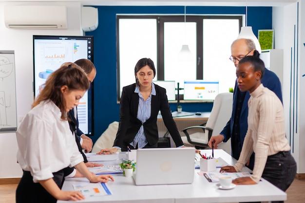 Grupo de diversos empresários reunidos para debater ideias sobre um novo projeto financeiro de papelada