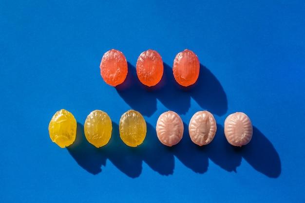 Grupo de doces coloridos organizados em linhas sobre fundo azul. contraste as sombras duras. conceito de loja de confeitaria e doces. foto.