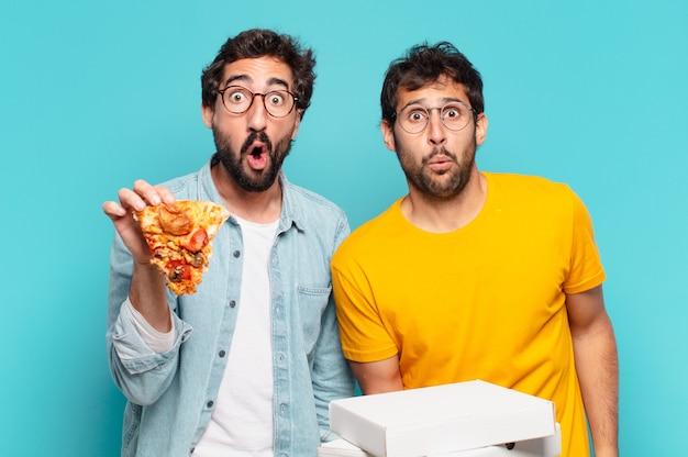 Grupo de dois amigos hispânicos com expressão de medo e segurando pizzas para levar