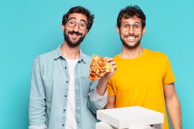 Grupo de dois amigos hispânicos com expressão feliz e segurando pizzas para levar