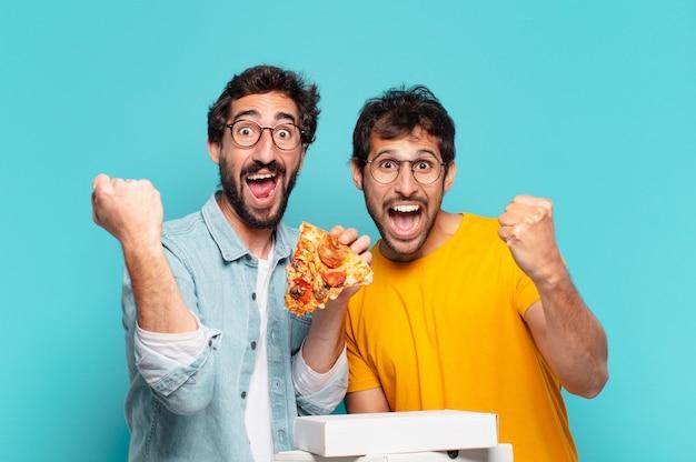Grupo de dois amigos hispânicos comemorando uma vitória bem-sucedida e segurando pizzas para levar