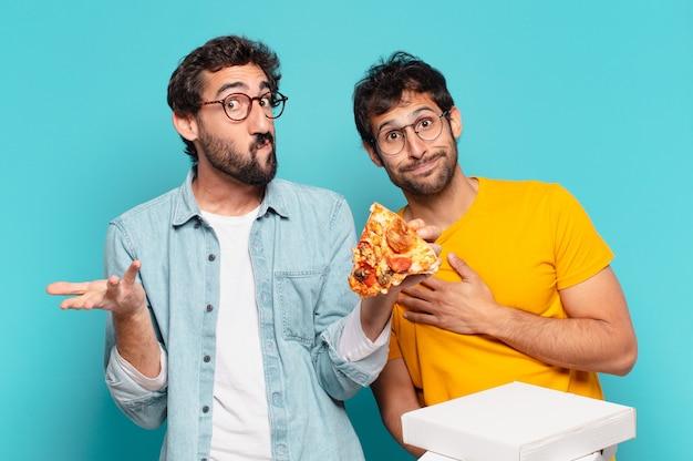 Grupo de dois amigos hispânicos duvidando ou com uma expressão incerta e segurando pizzas para levar