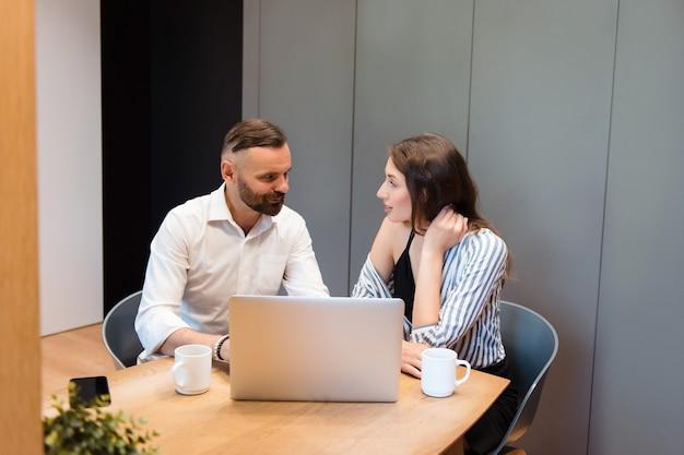 Grupo de dois colegas de trabalho sentados à mesa com café fresco