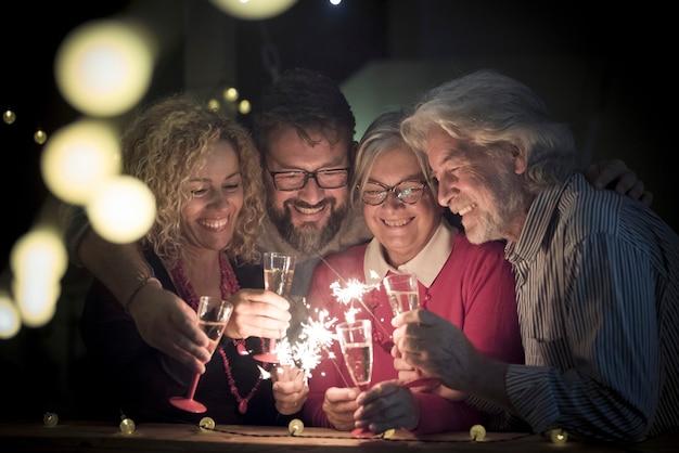 Grupo de dois idosos e dois adultos juntos se divertindo com os sparlers o ano novo para comemorar - família feliz com luzes à meia-noite