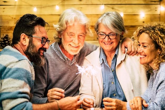 Grupo de dois idosos e dois adultos juntos se divertindo com os sparlers o ano novo para comemorar - família feliz com luzes