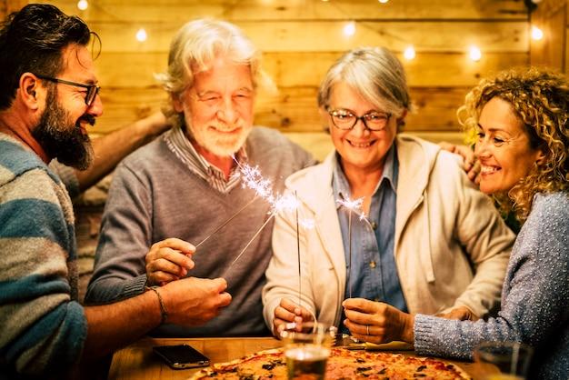 Grupo de dois idosos e dois adultos se divertindo com os sparlers o ano novo para comemorar - família feliz com luzes - comendo pizza no almoço
