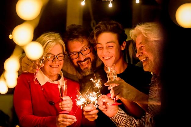 Grupo de dois idosos e dois adultos se divertindo com os sparlers o ano novo para comemorar - família feliz com luzes - segurando uma taça de champanhe