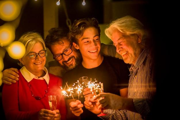 Grupo de dois idosos e um adulto e um adolescente se divertindo com os sparlers o ano novo para comemorar - família feliz com luzes