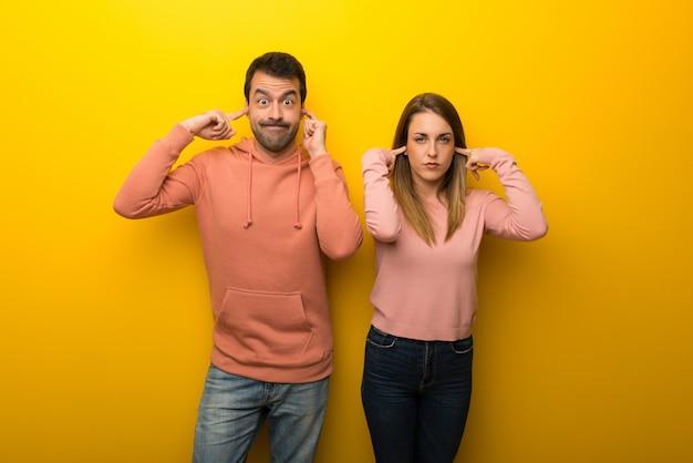 Grupo de duas pessoas em fundo amarelo, cobrindo ambas as orelhas com as mãos