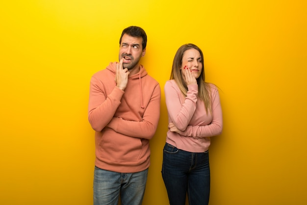 Grupo de duas pessoas em fundo amarelo com dor de dente